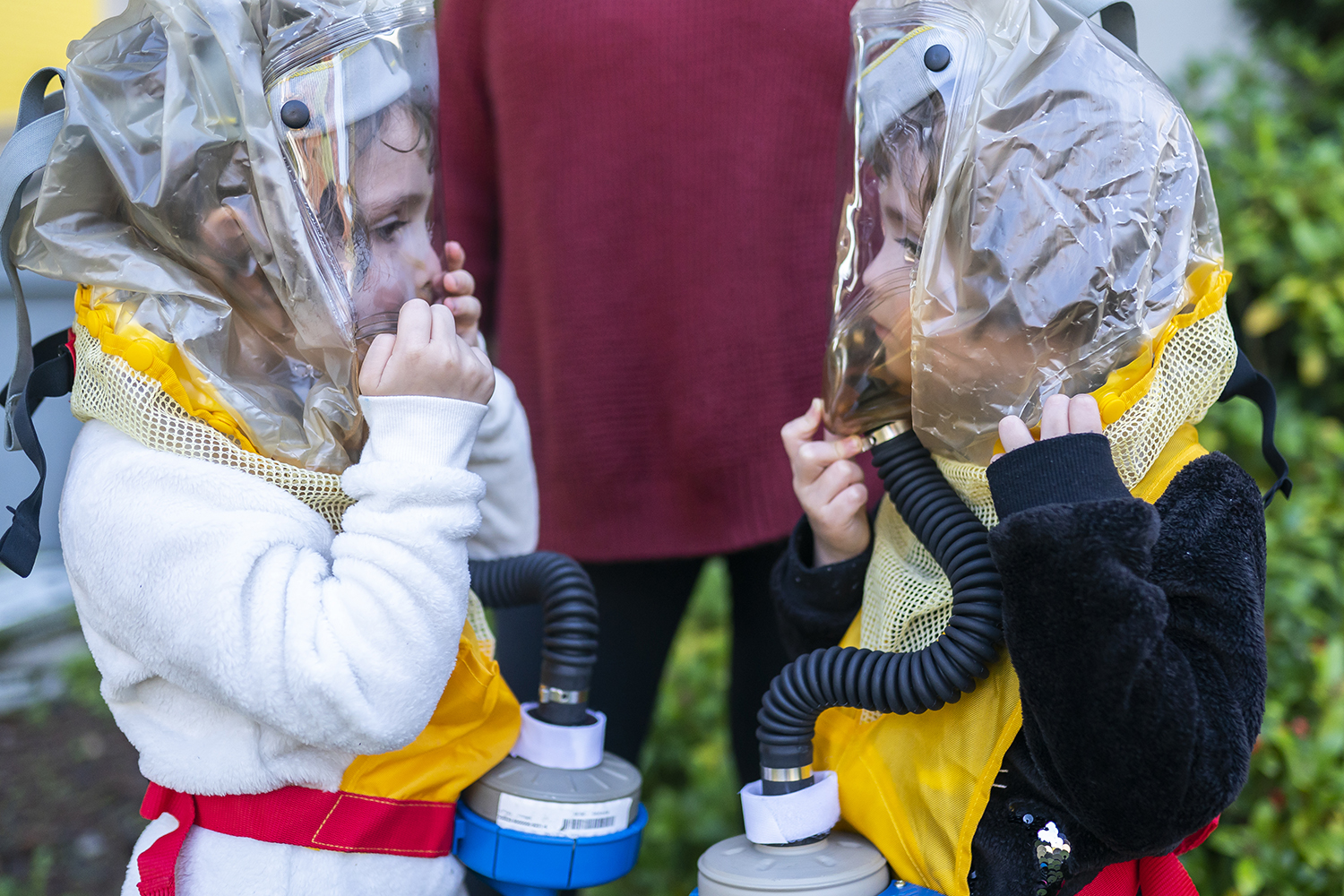 "Four-year-old twins Buddy Mae Walker, left, and Eleanor Walker examine each other through child respirators provided by the nonprofit Team Raccoon PDX in Portland, Oregon, on Oct. 6. Their mother, Jessica Walker, told the twins that their grandparents sent them ""space suits"" to keep them safe. The family sought out the respirators after police used tear gas near their residential street. Nathan Howard/Getty Images"