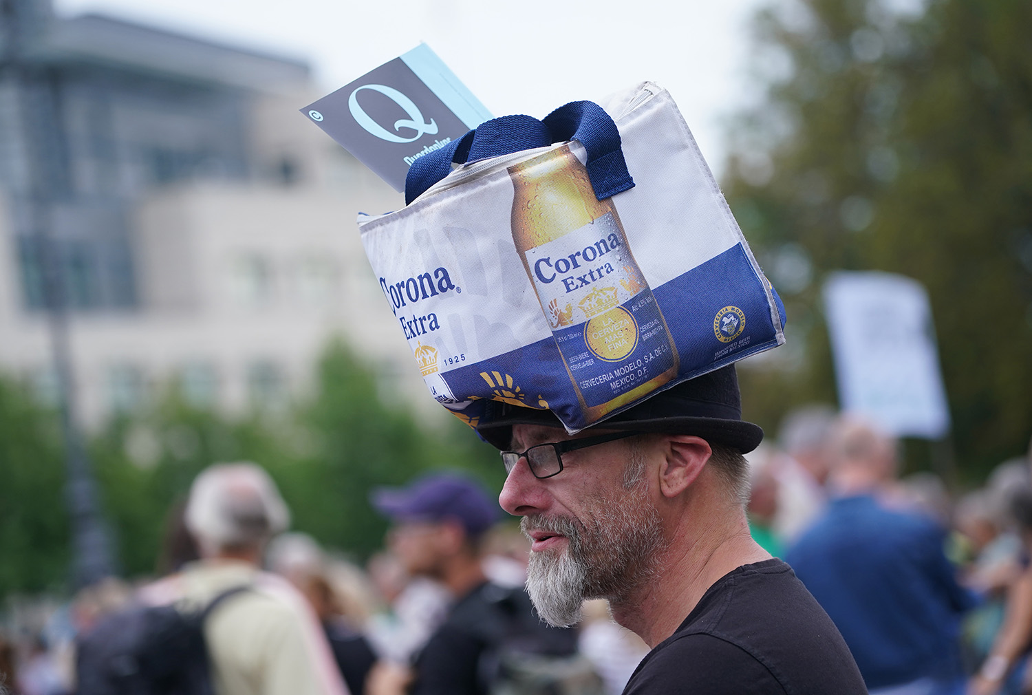A man wearing a Corona beer bag and a Querdenker Q flag attends a gathering of coronavirus skeptics on the eve of a planned protest march in Berlin on Aug. 28. The Querdenker group sees the pandemic as a conspiracy, and many Querdenker followers sympathize with the QAnon movement.