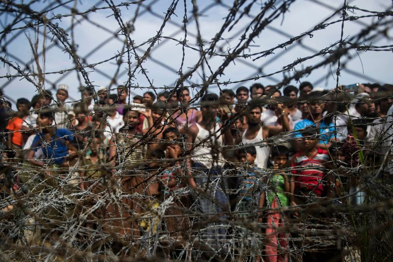 Rohingya refugees gather behind a barbed wire fence in a temporary settlement set up in the border zone between Myanmar and Bangladesh on April 25, 2018.