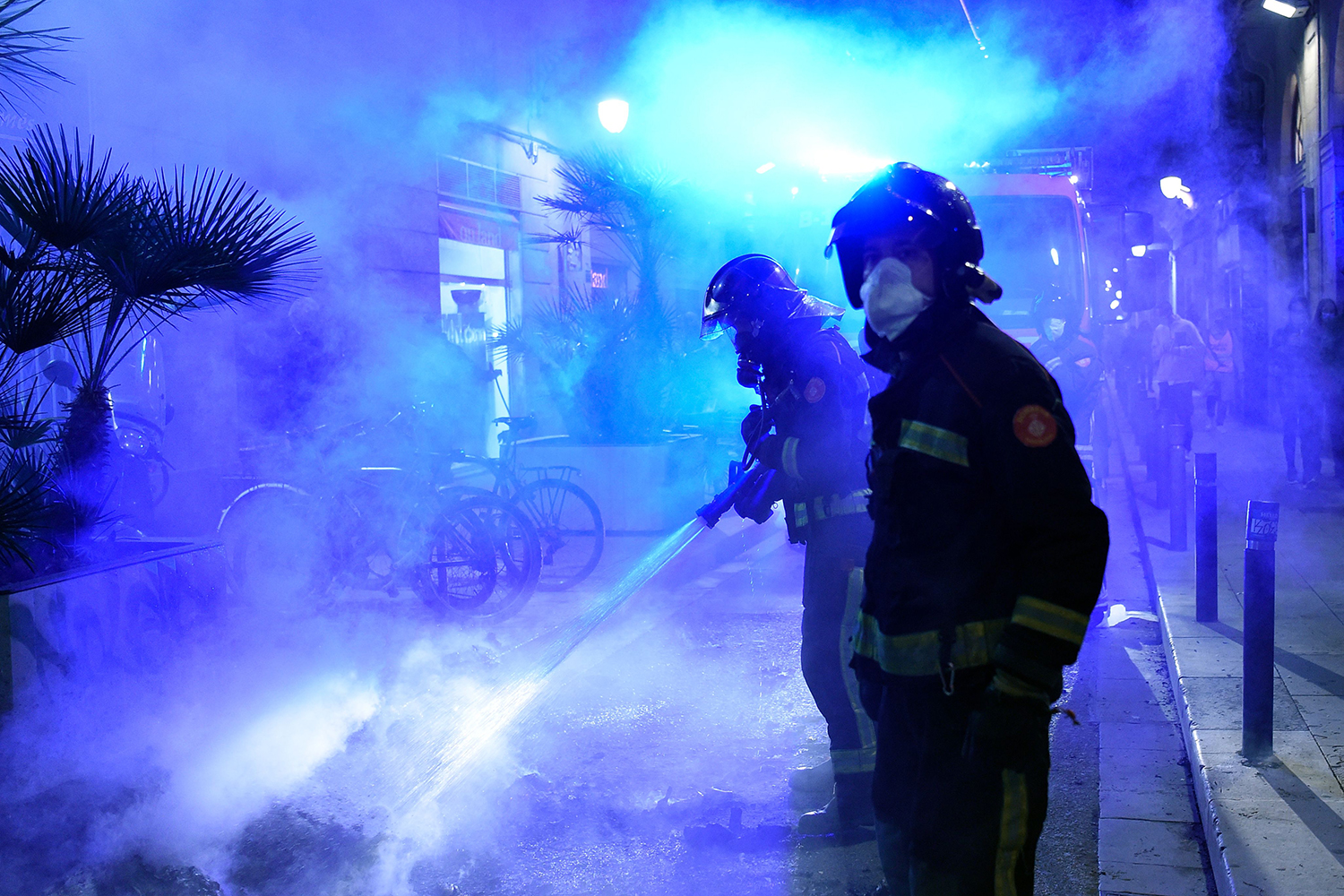Firefighters put out a blaze during a demonstration against the government's pandemic regulations in Barcelona, Spain, on Oct. 26. Spain's Catalonia region said it was looking into imposing a lockdown on weekends to fight the spread of the coronavirus, a day after a nighttime curfew came into effect across the country, sparking protests. JOSEP LAGO/AFP via Getty Images