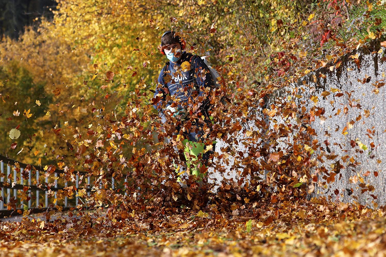 A worker blows leaves from a walkway on a crisp fall day near Stallikon, Switzerland, on Oct. 27. Arnd Wiegmann/REUTERS