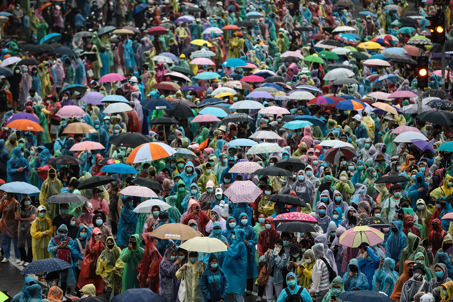 Pro-democracy protesters shelter from the rain during an anti-government rally at Victory Monument in Bangkok on Oct. 18. JACK TAYLOR/AFP via Getty Images