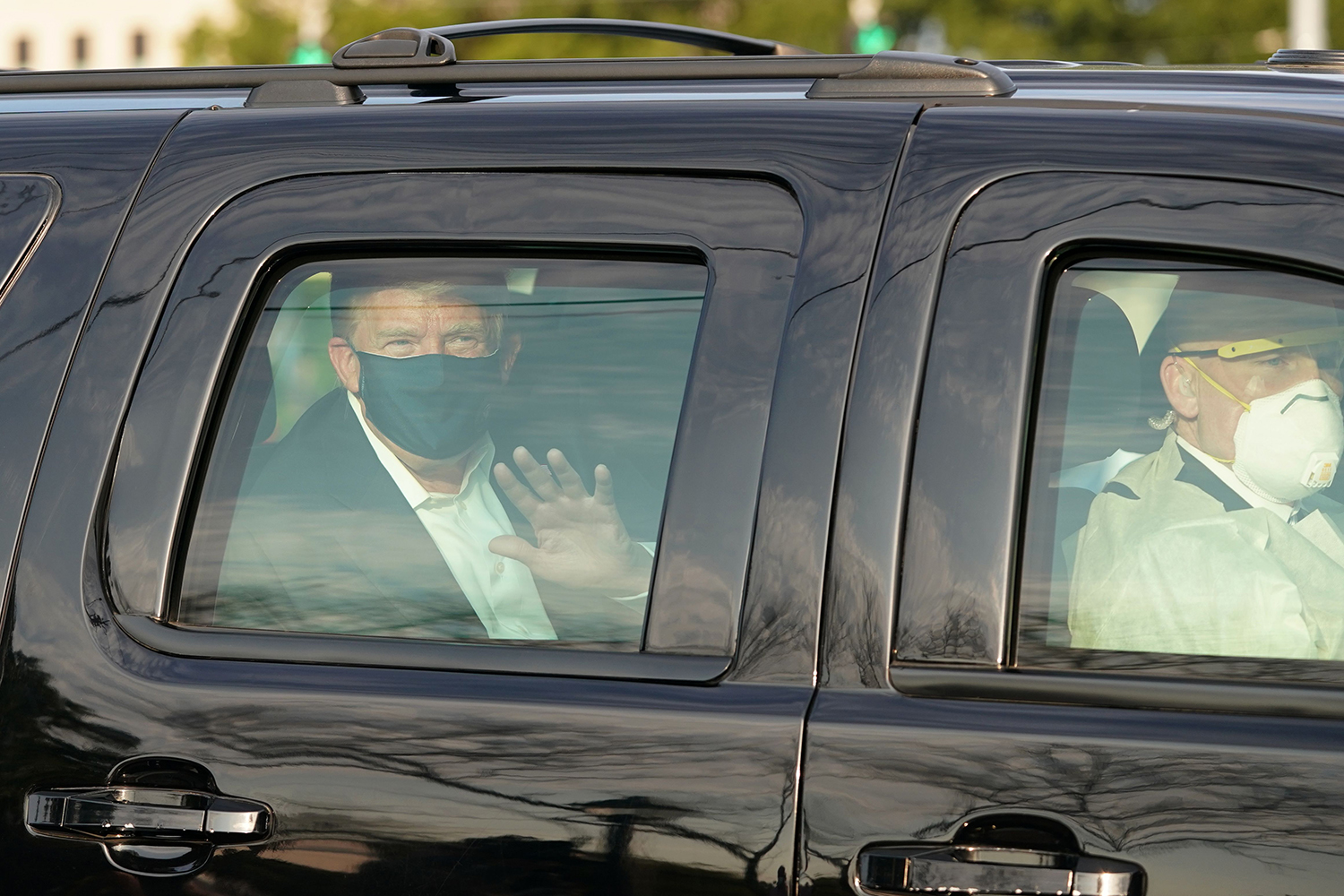 U.S. President Donald Trump waves from the back of a car outside Walter Reed National Military Medical Center in Bethesda, Maryland, on Oct. 4. Though hospitalized with COVID-19, the president said he wanted to thank supporters in a drive-by visit. ALEX EDELMAN/AFP via Getty Images