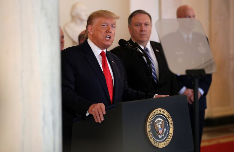 Secretary of State Mike Pompeo stands next to President Donald Trump as he speaks.