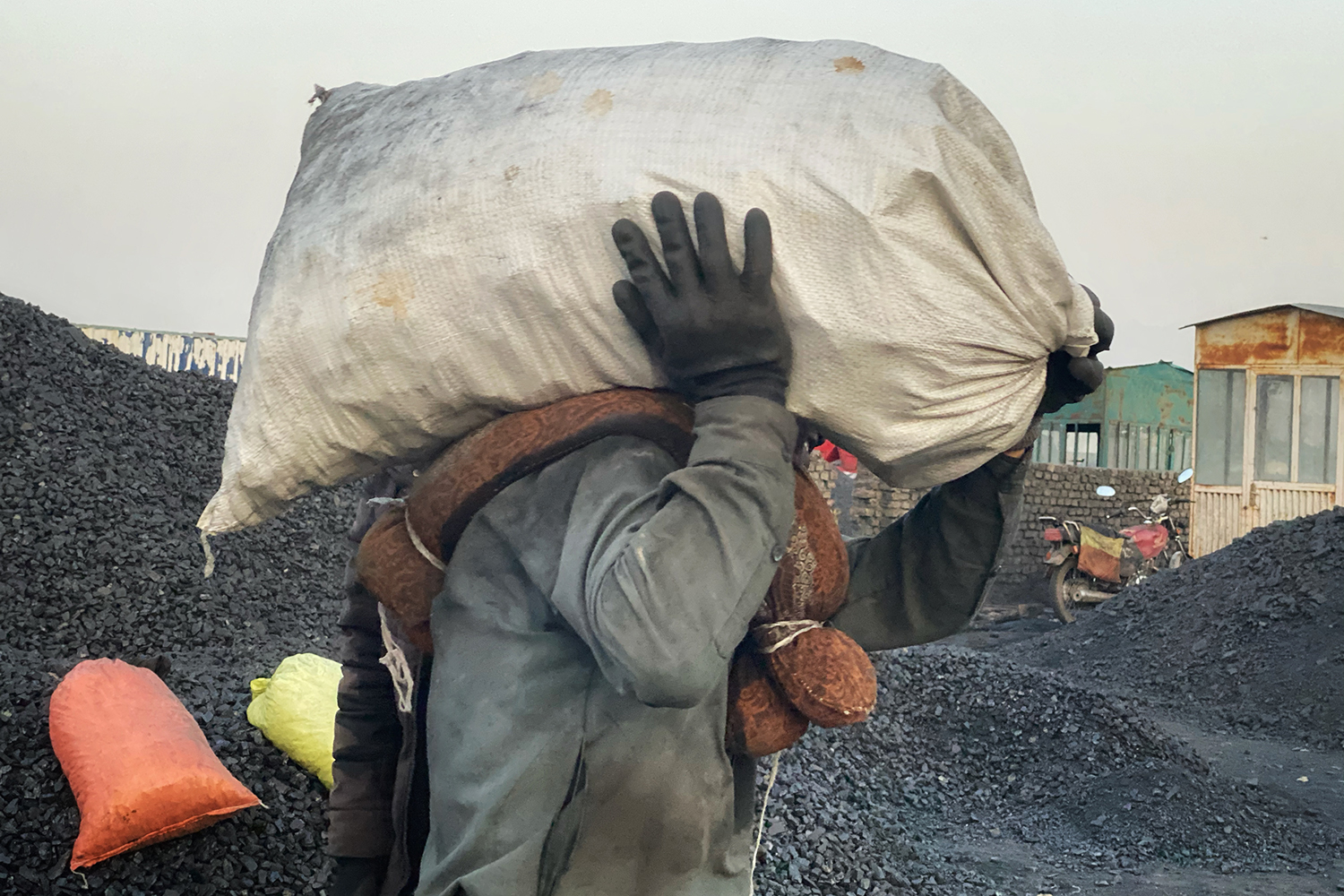 A coal trader lifts bags at a coal distribution workshop in the northern city of Mazar-i-Sharif, Afghanistan, on Sept. 26.
