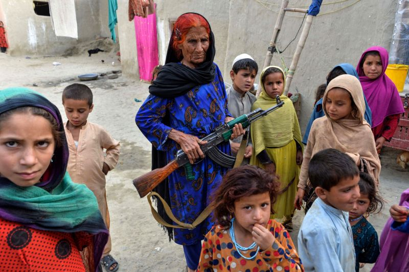 An Afghan woman holds a weapon as she stands among orphaned children at their home in the Kot district of Nangarhar province in Afghanistan on April 22, 2019.
