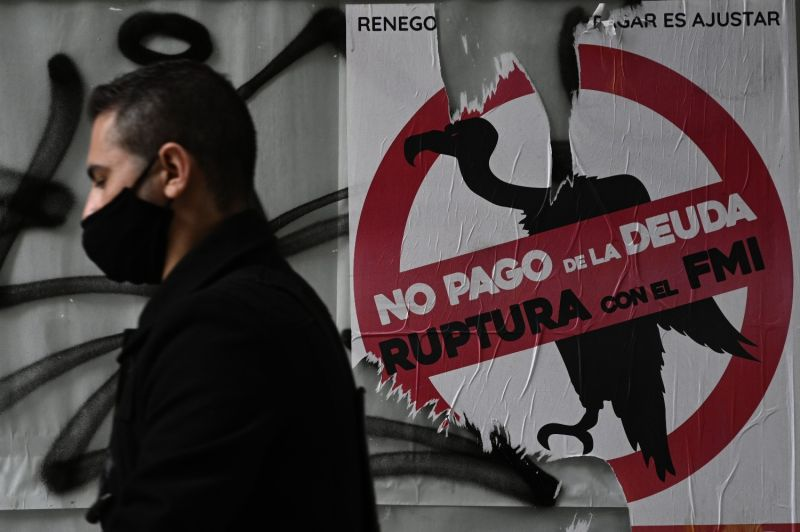 A man walks by a sign opposing debt repayments to the IMF during the coronavirus lockdown in Buenos Aires on May 22.