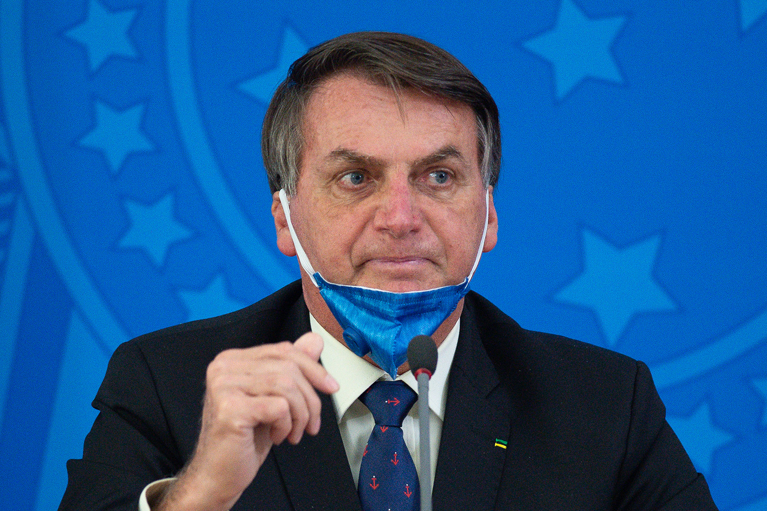 Brazilian President Jair Bolsonaro takes off his protective mask to speak to journalists during a news conference about the coronavirus outbreak at the Planalto Palace in Brasilia on March 20.