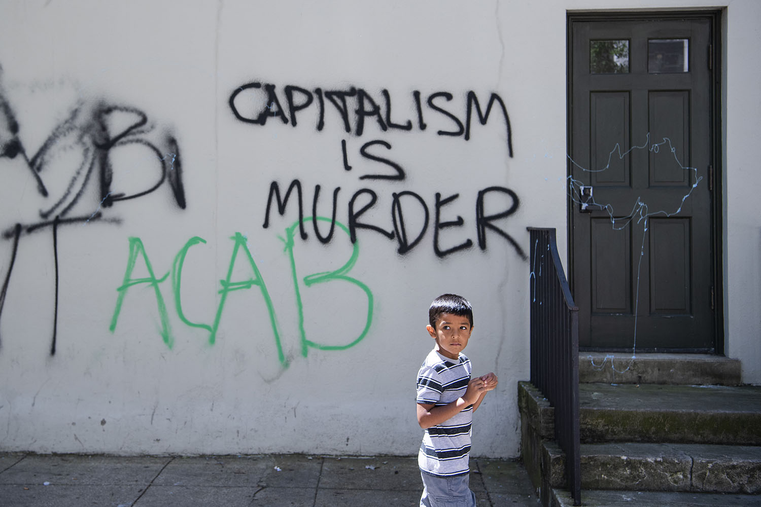 A child walks by graffiti on H St. NW near the White House in Washington on June 1, after protests sparked by the killing of George Floyd.