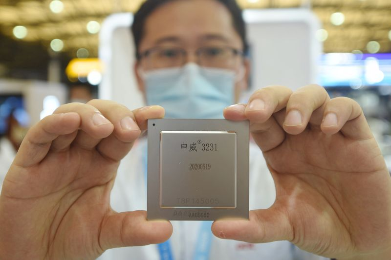 A worker presents a domestically developed chip at the stand of China Electronics Technology Group Corp. during the China International Semiconductor Expo in Shanghai on Oct. 14.