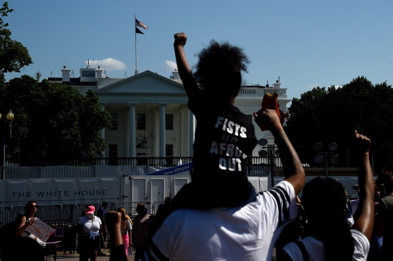 Protesters hold up their fists up in Lafayette Park, across from the White House, to protest against police brutality and racial injustice on June 14.