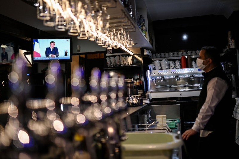 French President Emmanuel Macron is seen on a TV screen in a cafe in Marseille, southern France, on October 28, 2020.