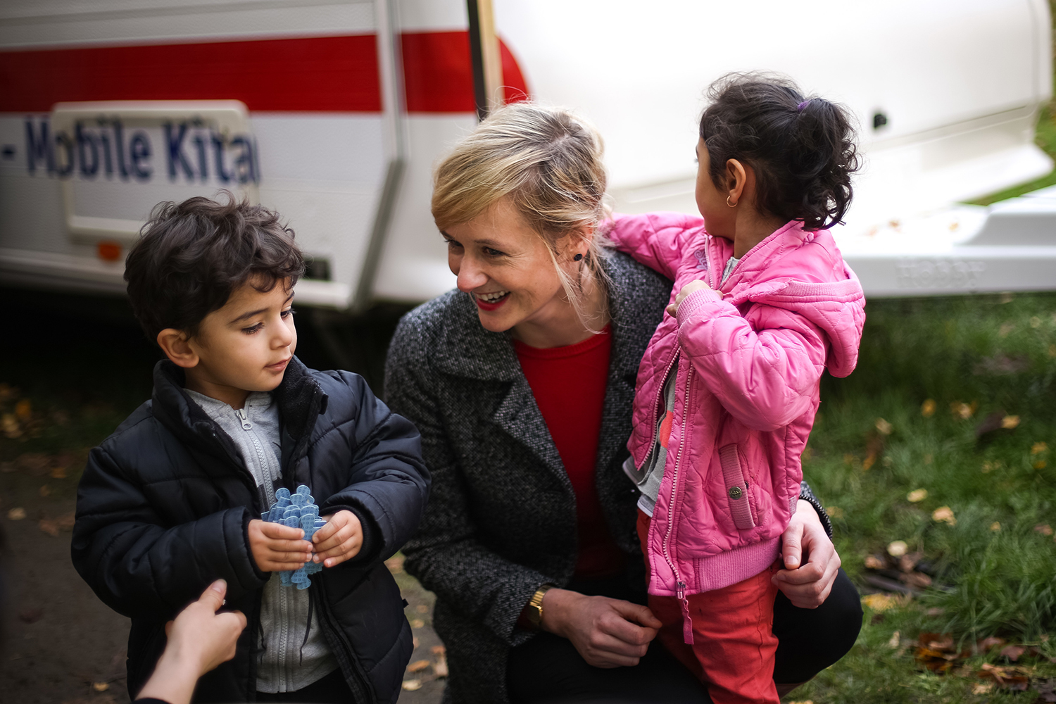 Christina Kampmann, then-family minister of North Rhine-Westphalia, speaks with two children from Syria in Gelsenkirchen, Germany, on Oct. 26, 2015.