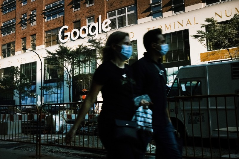 Pedestrians walk by Google's offices in downtown Manhattan on Oct. 20.