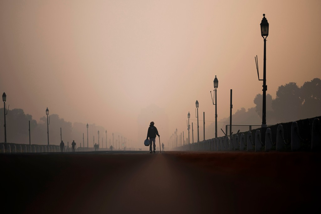 A man walks along a street near India Gate amid heavily polluted conditions in New Delhi on Dec. 6, 2019.