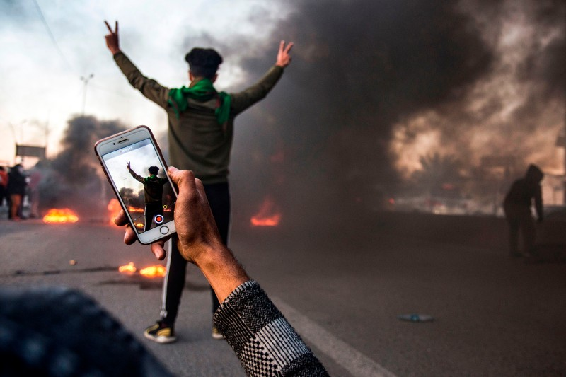 An Iraqi protester uses his phone to film another next to burning tires while blocking a road during a demonstration against corruption and lack of services in the southern city of Basra on Jan.  11, 2019.
