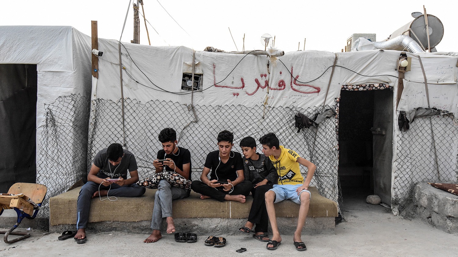 Boys look at smartphones as they sit outside a cafeteria tent at a camp for internally displaced persons in the Sharya area, in the autonomous Iraqi Kurdistan region, on Aug. 30, 2019.