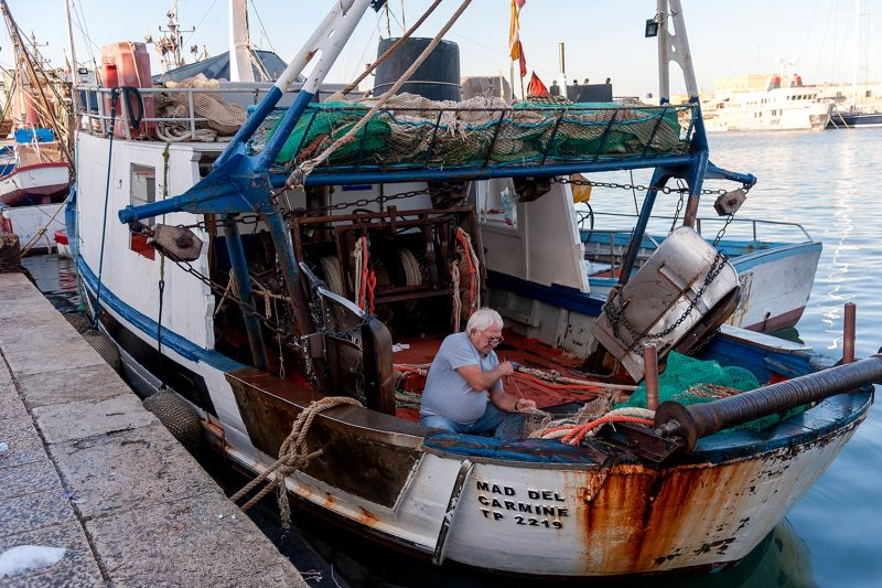 A fisherman mends his nets on a fishing boat in Trapani harbor in Sicily on Sept. 7, 2017.
