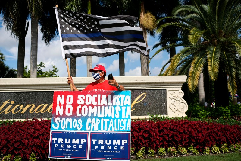 "A supporter of U.S. President Donald Trump rallies outside the ""Latinos for Trump Roundtable"" event at Trump National Doral Miami golf resort in Doral, Florida, on Sept. 25."
