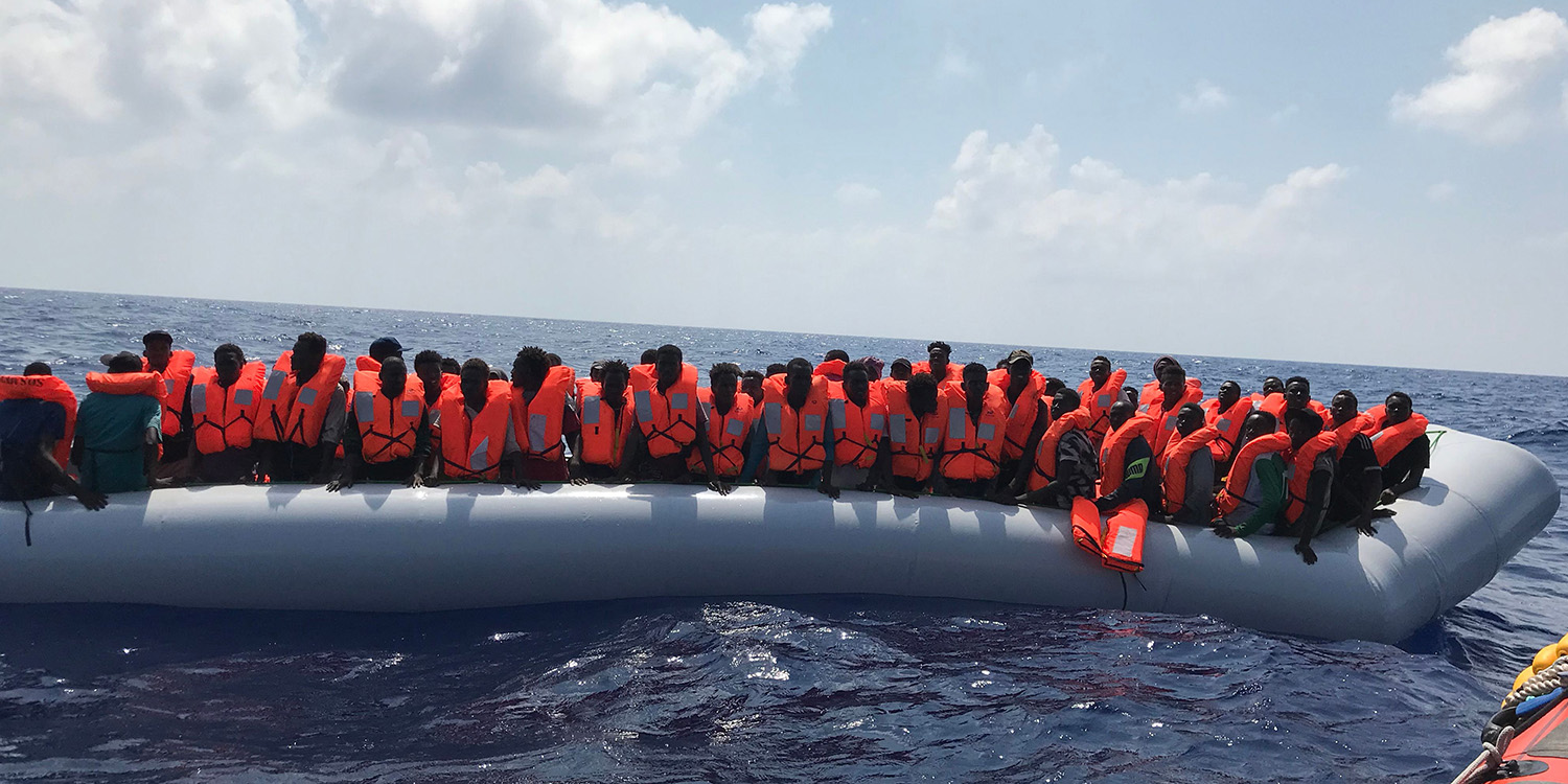 Migrants stand on an inflatable boat during a rescue operation by a French NGO in the Mediterranean Sea on Aug. 10, 2019.