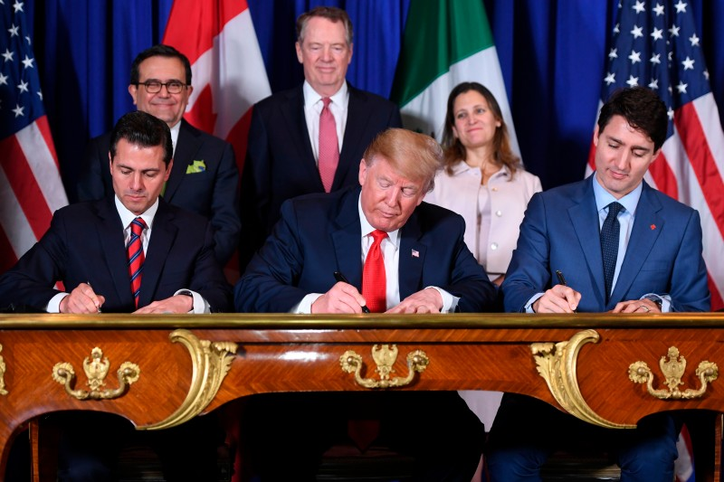 Mexican then-President Enrique Pena Nieto, U.S. President Donald Trump, and Canadian Prime Minister Justin Trudeau sign a revised trade agreement on the sidelines of the G20 summit in Buenos Aires, on Nov. 30, 2018.