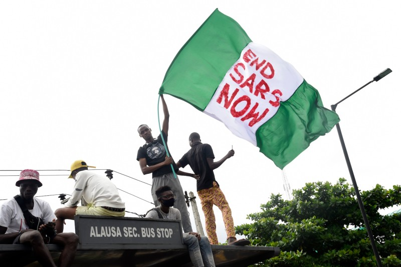 A protester waves the Nigerian national flag while gathering with other protesters to barricade the Lagos-Ibadan expressway.