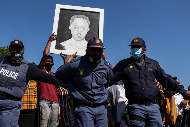 South African police officers hold protesters back during the funeral procession for Nathaniel Julies—who was shot by police—in Eldorado Park, near Johannesburg, on Sept. 5.