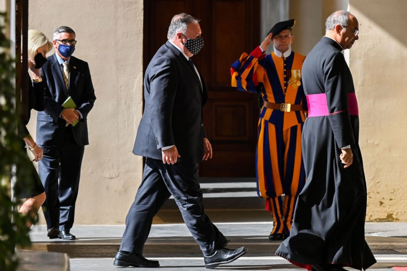 U.S. Secretary of State Mike Pompeo (C), followed by U.S. Ambassador to the Holy See Callista Gingrich, walks past a Swiss Guard as he arrives on October 1, 2020 after being welcomed by Monsignor Guillermo Karcher (R) at San Damaso courtyard in The Vatican.