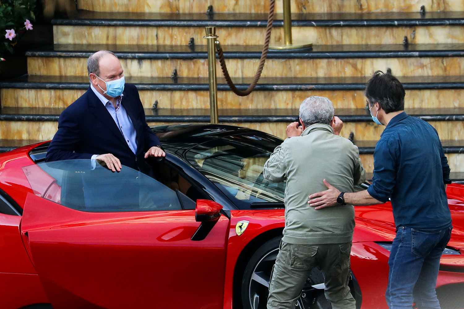 French director Claude Lelouch films Monaco's Prince Albert II as he gets in a Ferrari while filming a short movie in Monaco on May 24.