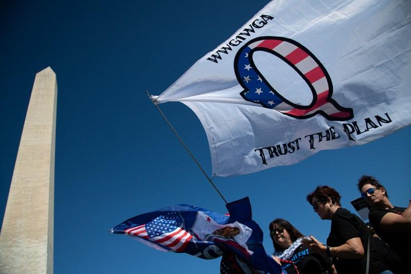 A protester waves a QAnon flag