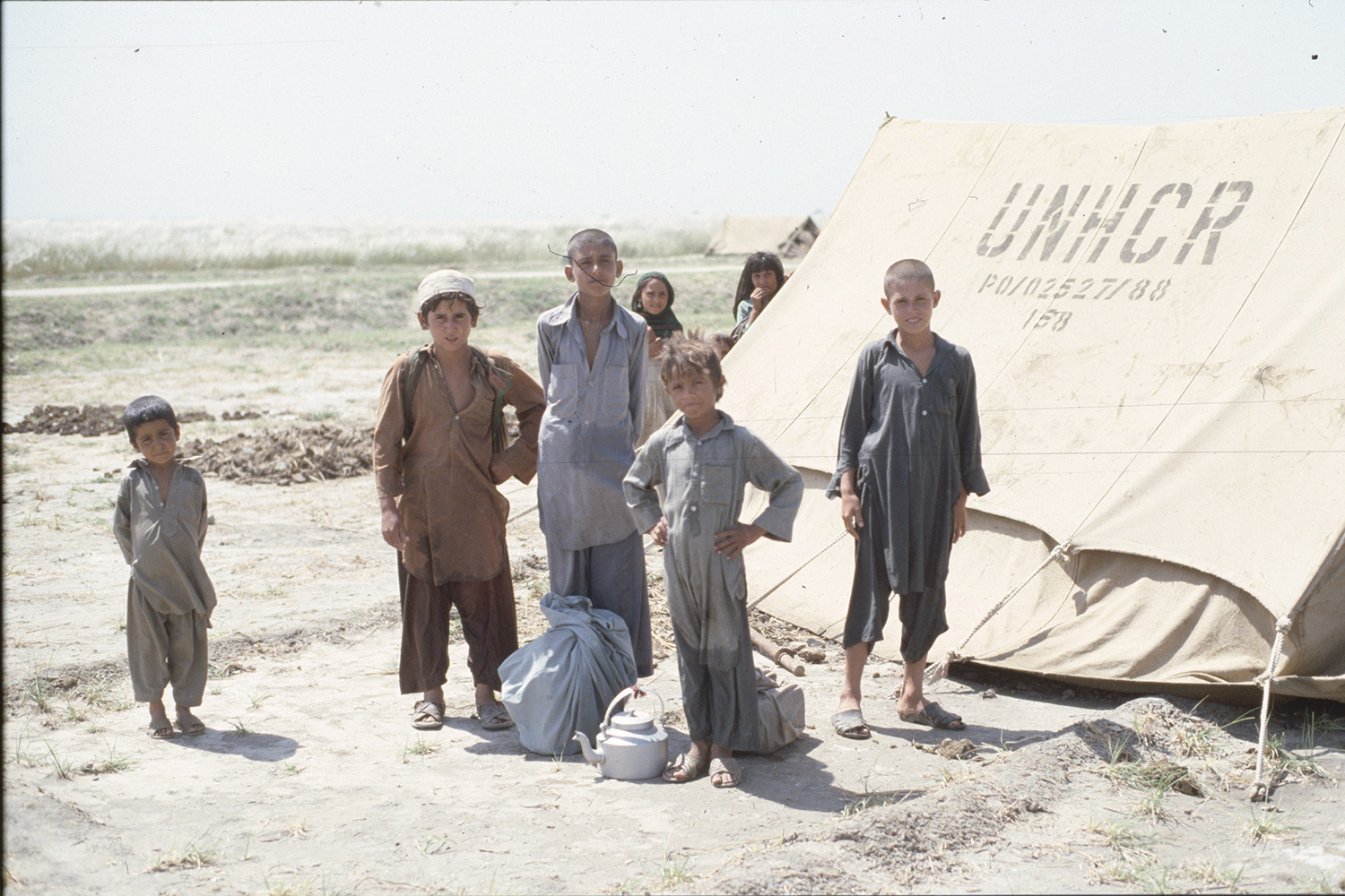 A group of young Afghan boys stand outisde a tent supplied by the Office of the United Nations High Commissioner for Refugees at a camp in Pakistan on Jan. 1, 1989.