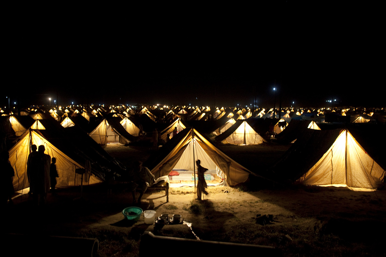 Tents tightly packed together are lit up at night at the Shah Mansoor relief camp in Swabi, Pakistan, on June 21, 2009.
