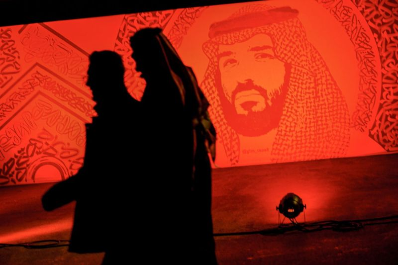 Young Saudis walk next to a portrait of Crown Prince Mohammed bin Salman at the Riyadh Season Boulevard in the Saudi capital on Jan. 31.