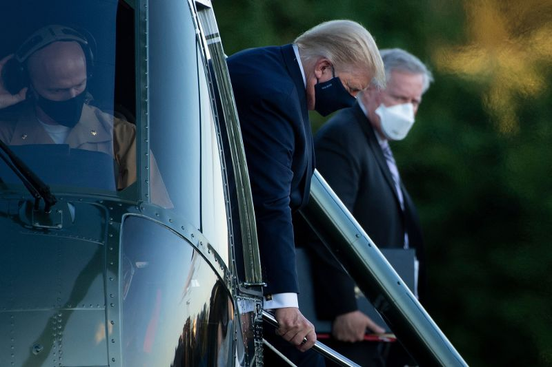 White House chief of staff Mark Meadows (right) watches as U.S. President Donald Trump walks off Marine One upon arrival at Walter Reed Medical Center in Bethesda, Maryland, on Oct. 2 following the president's COVID-19 diagnosis.
