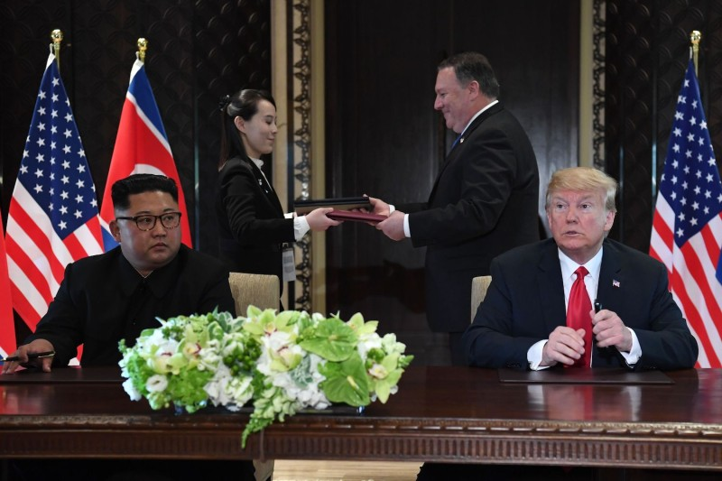U.S. President Donald Trump and North Korean leader Kim Jong Un look on as documents are exchanged between U.S. Secretary of State Mike Pompeo and Kim's sister, Kim Yo Jong, during a signing ceremony in Singapore on June 12, 2018.
