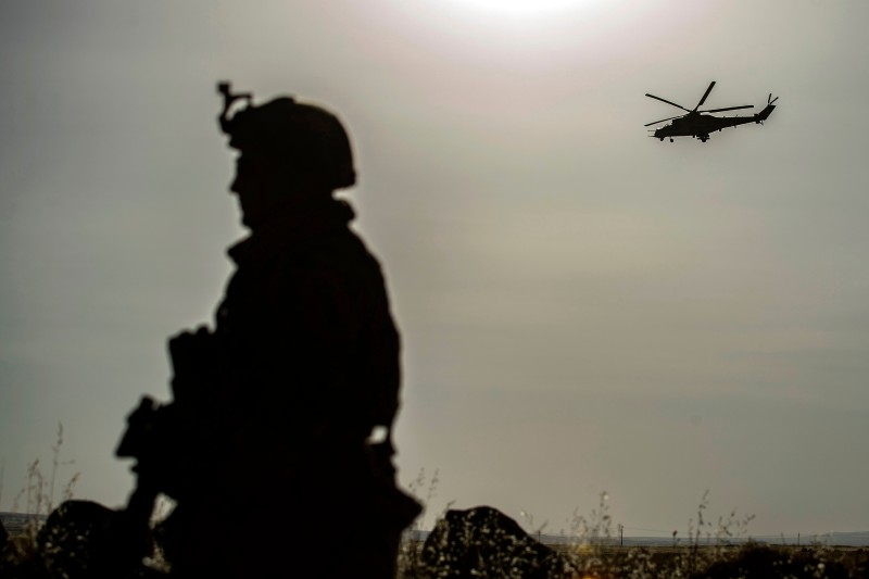 A U.S. soldier stands guard as a Russian Mil Mi-24 helicopter gunship flies over the Syrian town of Al-Malikiyah near the Turkish border on June 3.