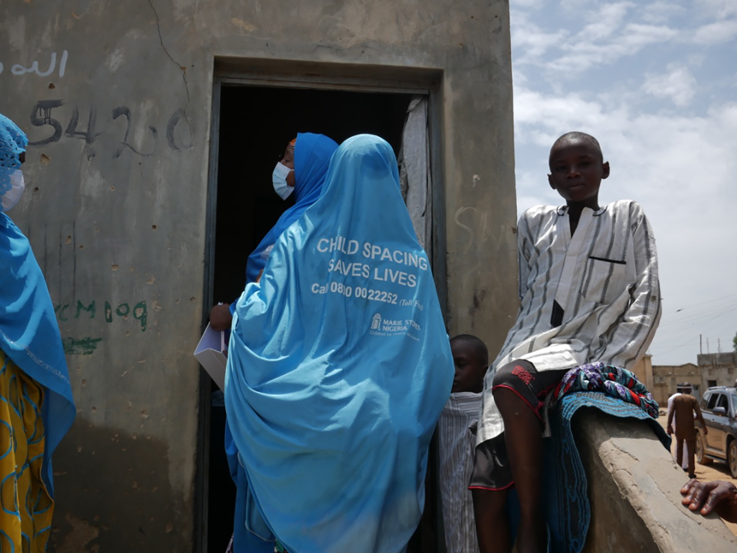Two nurses employed by Marie Stopes Nigeria enter a compound to administer family planning services in Kano on Aug. 14. The women come around 1 p.m., which coincides with the Friday congregational prayer that all men must attend, enabling their wives to more freely talk about their needs.