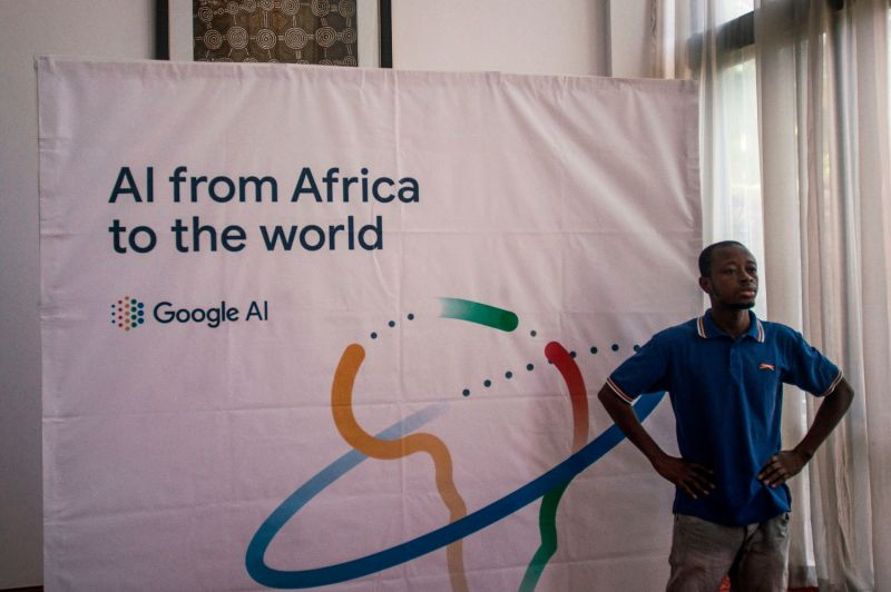 A worker stands in front of a banner for Google AI during a presentation marking the opening of the first artificial intelligence center in Africa in Accra, Ghana, on April 10, 2019.