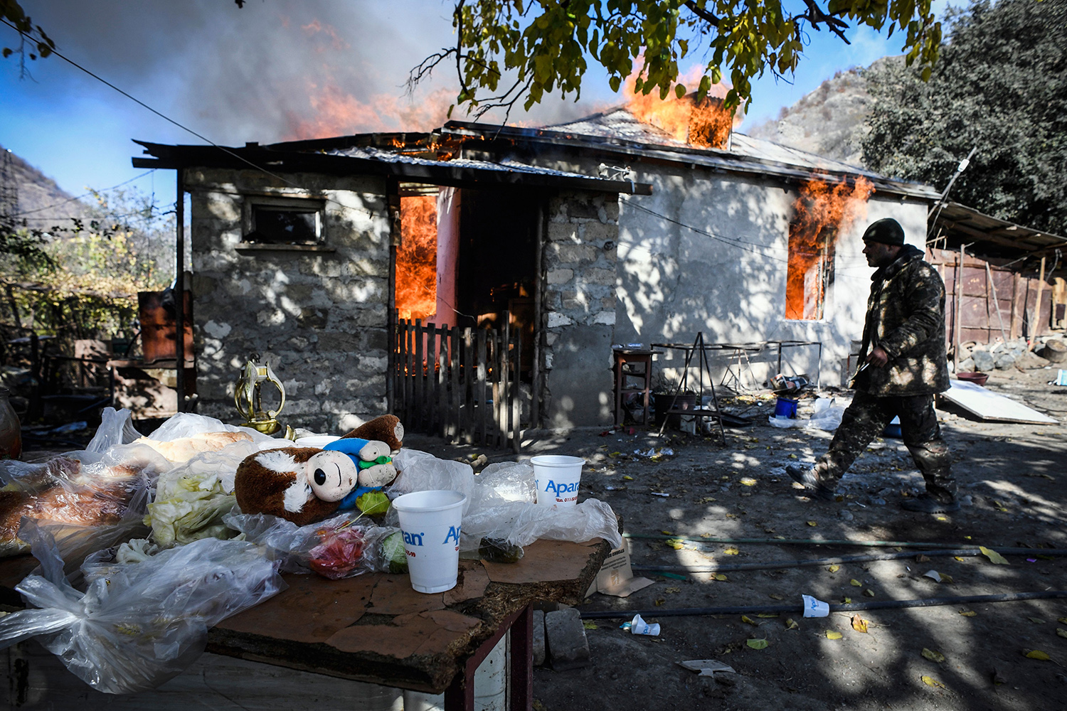 A man walks past a house as it burns in the village of Charektar, outside of Kalbajar, on Nov. 14 during the military conflict between Armenia and Azerbaijan over the breakaway region of Nagorno-Karabakh. Villagers in Nagorno-Karabakh set their houses on fire before fleeing to Armenia ahead of a deadline to hand over parts of the territory to Azerbaijan as part of a peace agreement. ALEXANDER NEMENOV/AFP via Getty Images