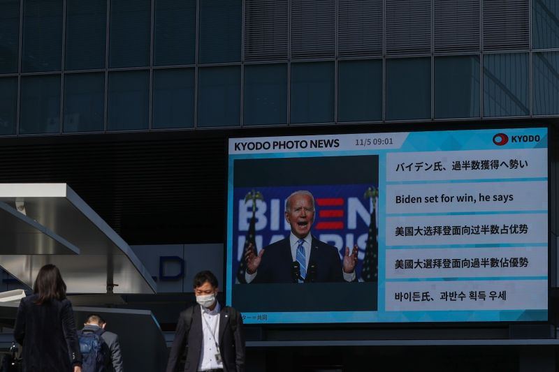 A screen showing Joe Biden in Tokyo