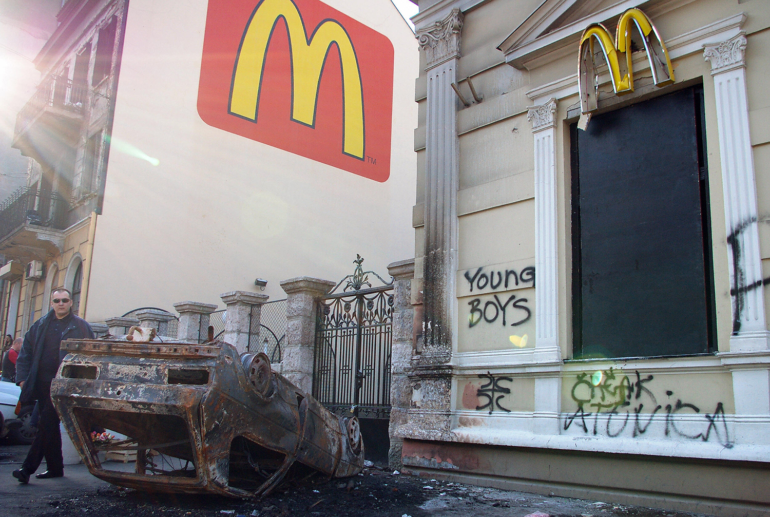 A pedestrian walks by a burned car in front of McDonald's restaurant after unrest in downtown Belgrade on Feb. 22, 2008.