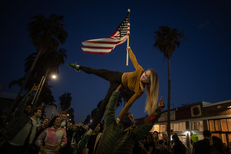 People dance in the Venice Beach neighborhood of Los Angeles on Nov. 7 as they celebrate the declaration of Joe Biden as winner of the 2020 U.S. presidential election. APU GOMES/AFP via Getty Images