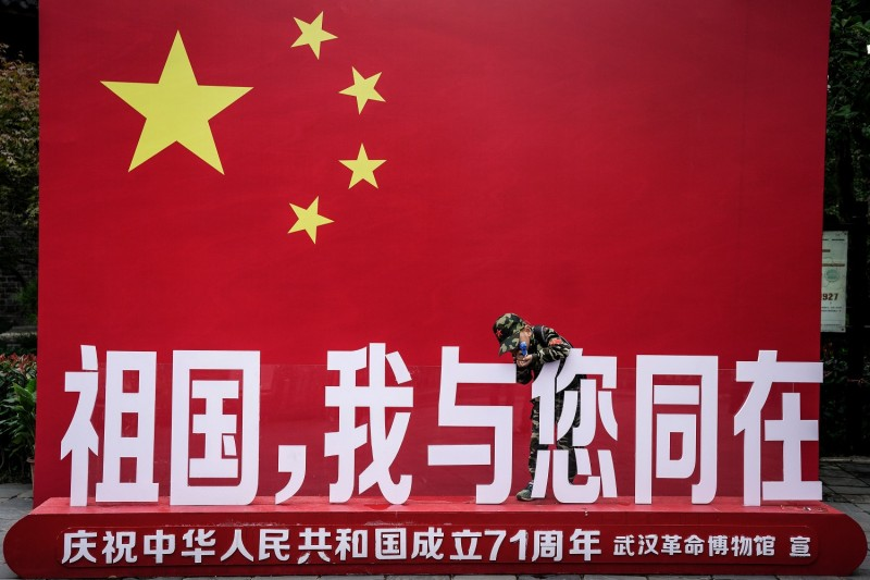 A boy plays in front of the Chinese flag at Wuhan Revolution Museum in Wuhan, China, on Oct. 7.