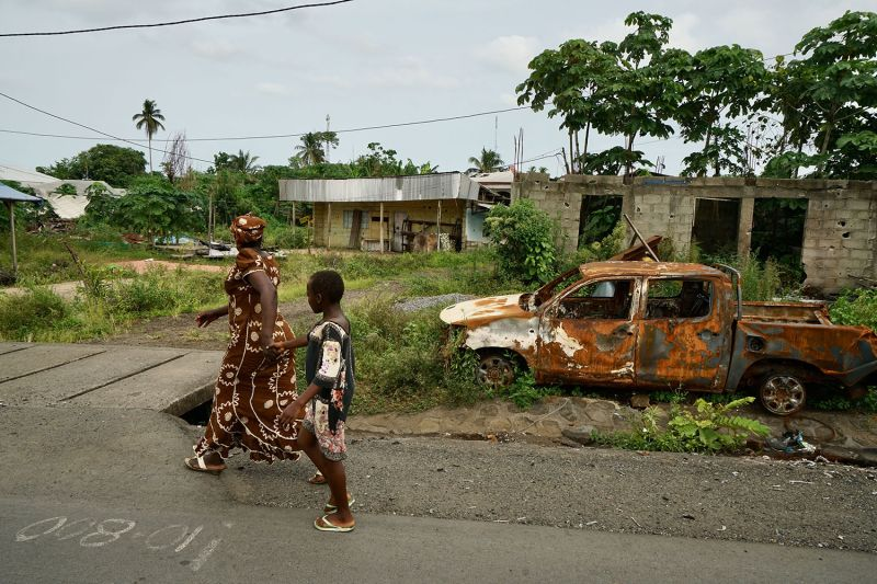 A mother and child walk past a destroyed car in a small town on the main highway near Buea on May 11, 2019.  The location is one of many residential areas that now sit empty as residents flee to the main city of Buea or into the deep tropical forests after violence in the region.