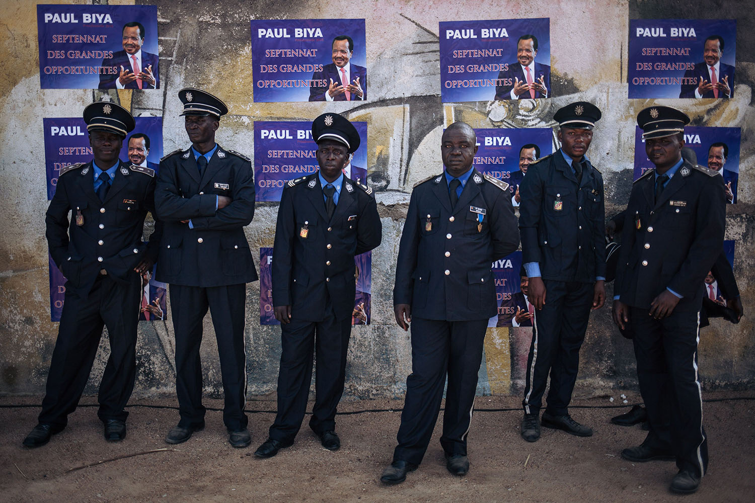 Policemen wait in the shade after the electoral meeting in front of posters for President Paul Biya in Maroua on Sept. 29, 2018.