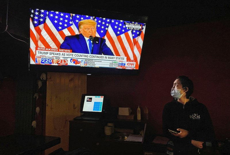 A waitress watches a speech by U.S. President Donald Trump on a television during at a local bar on Nov. 4, 2020 in Beijing, China.