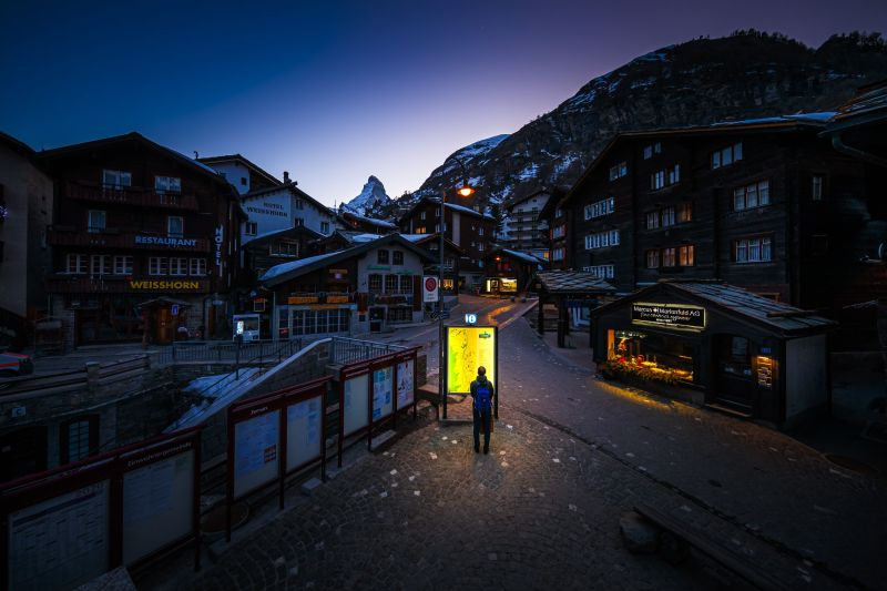 A pedestrian looks at an illuminated map board in the empty streets of the Alpine resort of Zermatt, with the Matterhorn mountain amid the spread of the COVID-19 caused by the novel coronavirus.