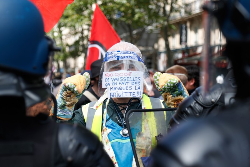 "A protester wearing a yellow vest, oven mitts and a protective visor with a sign reading ""500,000 euros of tableware, that's a lot of masks Brigitte""  faces gendarmes during a demonstration in Paris, on July 14, 2020."