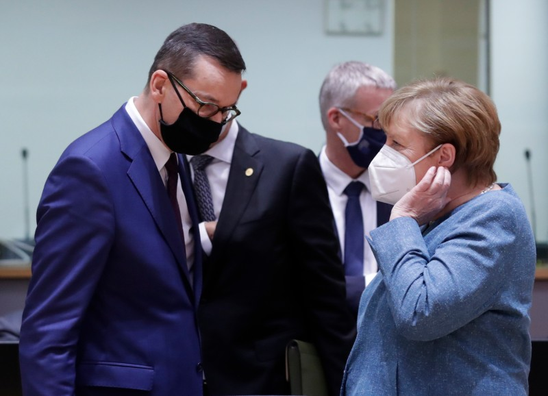 Poland's Prime Minister Mateusz Morawiecki and German Chancellor Angela Merkel speak together as they arrive for an EU summit at the European Council building in Brussels, on October 1, 2020.