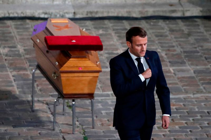 French President Emmanuel Macron pays his respects by the coffin of Samuel Paty's coffin inside Sorbonne University's courtyard in Paris on October 21, 2020, during a national homage to French teacher Samuel Paty, who was beheaded for showing cartoons of the Prophet Mohamed in his civics class.